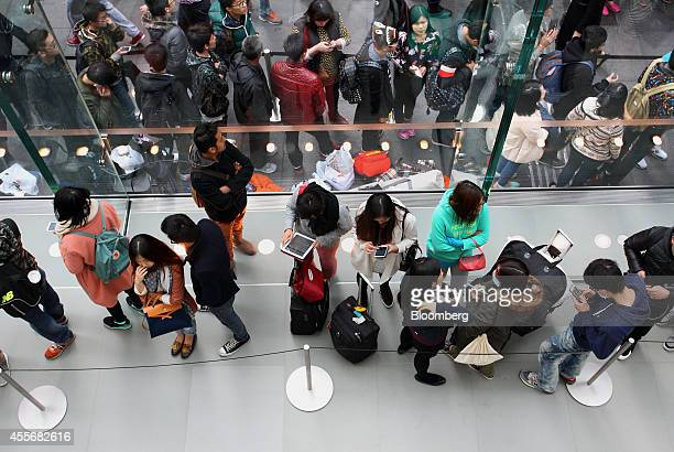 Customers use mobile devices while standing in line at the Apple Inc George Street store during the sales launch of the iPhone 6 and iPhone 6 Plus in...