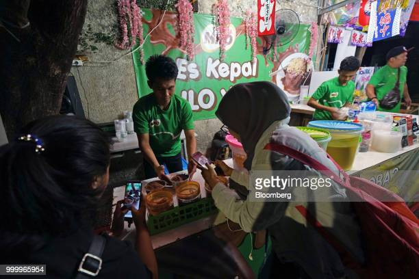 Customers use smartphones to take photographs as an employee presents an order of Milo on round ice snack at an Es Kepal Milo Viral street stall in...
