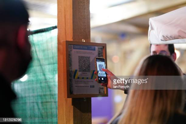 Customers use the track and trace app as they enter an outside seating area at the Switch bar in Newcastle as it prepares to serve customers after...