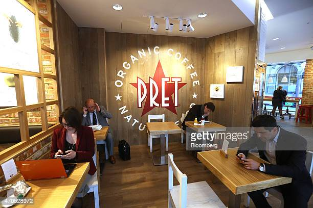 Customers use their mobile phones as they sit at tables inside a Pret A Manger sandwich store operated by private equity firm Bridgepoint in London...