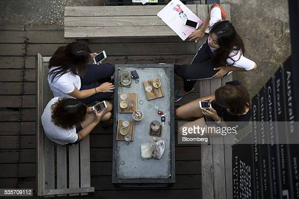 Customers use their smartphones while sitting at the Ristr8to Coffee store in Chiang Mai Thailand on Sunday May 29 2016 Thailand's gross domestic...