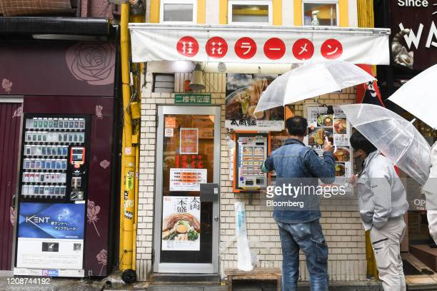 Customers using an umbrella check a lunch menu outside a ramen noodle shop in the Shinjuku district of Tokyo Japan on Wednesday April 1 2020 Japans...