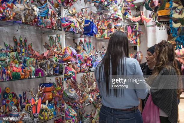 Customers view alebrijes Mexican folk art sculptures displayed for sale at the Ciudadela Market in Mexico City Mexico on Tuesday Oct 17 2017 The...