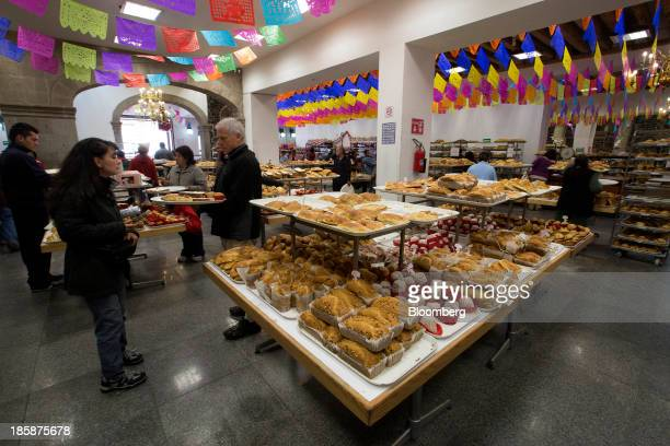 Customers view cakes and pastries at La Ideal bakery in Mexico City Mexico on Thursday Oct 24 2013 The pan de muerto or bread of the dead is a sweet...