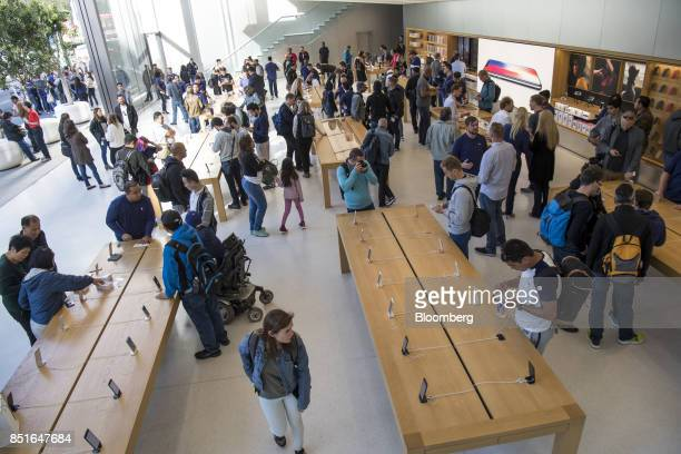 Customers view merchandise displayed during the sales launch of the Apple Inc iPhone 8 smartphone Apple watch series 3 device and Apple TV 4K inside...