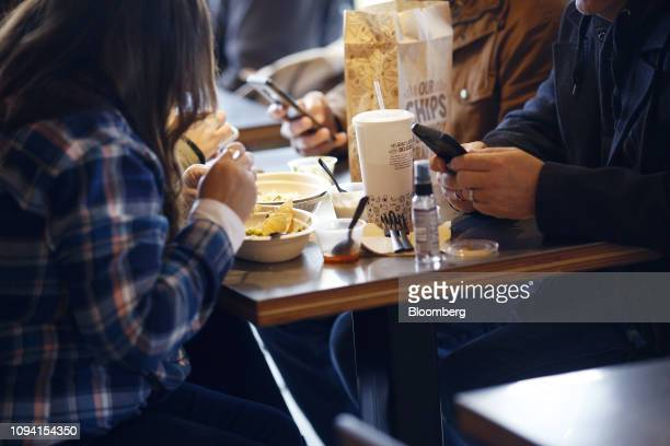Customers view mobile devices while eating food at a Chipotle Mexican Grill Inc restaurant in Louisville Kentucky US on Saturday Feb 2 2019 Chipotle...