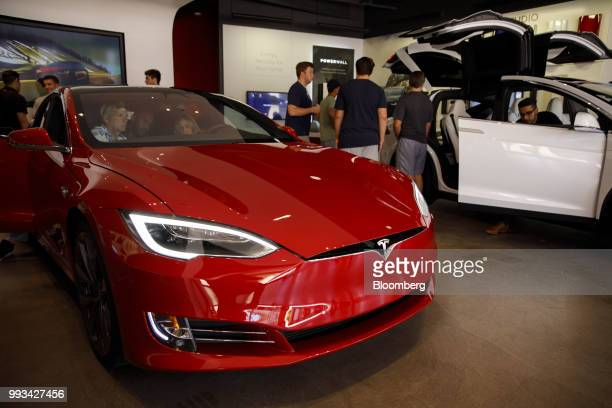 Customers view Tesla Inc Model S and Model X electric vehicles on display at the company's showroom in Newport Beach California US on Friday July 6...