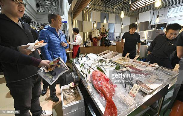 Customers visit the Tsukiji Uogashi commercial facility selling fish and fruit in Tokyo's Chuo Ward on Nov 19 its opening day The ward office built...