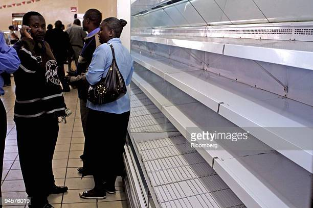 Customers wait alongside empty shelves at a supermarket in Harare Zimbabwe Monday July 23 2007 Zimbabwe's government extended price controls in the...