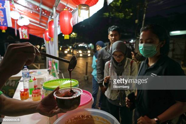 Customers wait as an employee pours molten milo chocolate over a bowl of crushed ice while preparing an order of Milo on round ice snack at an Es...