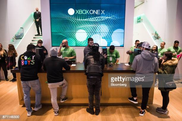 Customers wait at a counter to purchase the Xbox One X game consoles ahead of it's midnight release during the Microsoft Corp global launch event in...