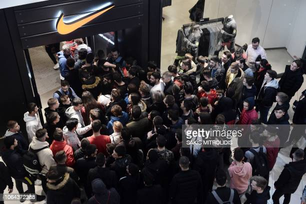 Customers wait at the entrance of a Nike sportswear store in Thessaloniki on November 23 at the start of the Black Friday sales Queues formed outside...