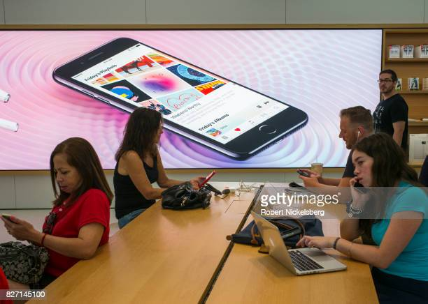 Customers wait for technical support August 5 2017 in front of an advertisement at the Apple retail store July 22 2017 inside the World Trade Center...