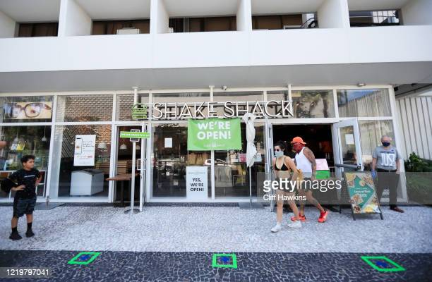 Customers wait for to-go orders outside Shake Shack in South Beach on April 19, 2020 in Miami Beach, Florida. Miami Beach restaurants are restricted...