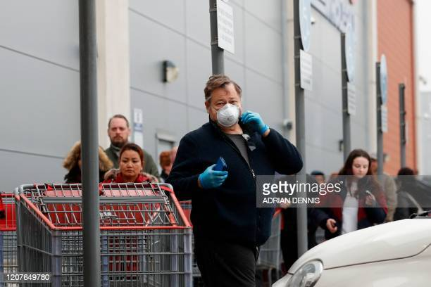Customers wait in a long queue to enter a Costco members wholesale outlet in Farnborough, west of London, on March 19, 2020. - Britain's supermarkets...