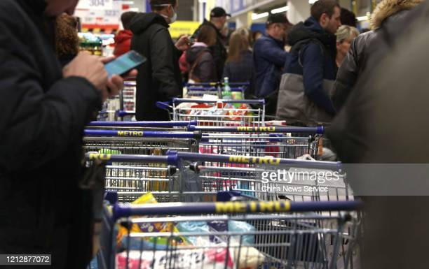 Customers wait in a queue to check out at a supermarket amid novel coronavirus outbreak on March 16 2020 in Moscow Russia