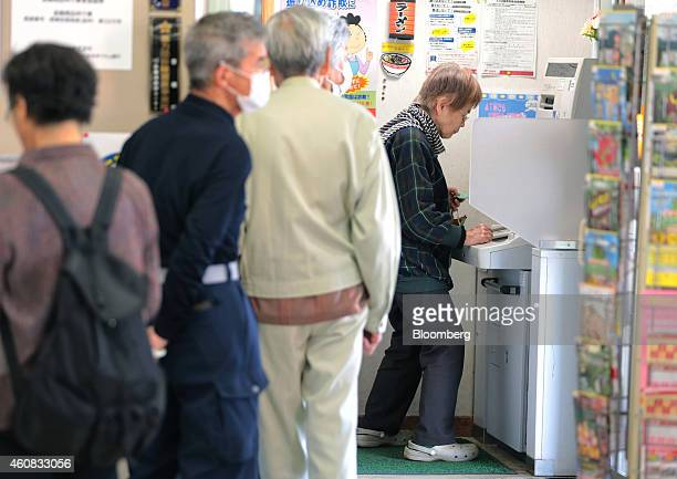 Customers wait in line as an elderly woman makes a withdrawal at an automated teller machine at a Japan Post Co branch in Hachioji Japan on Tuesday...