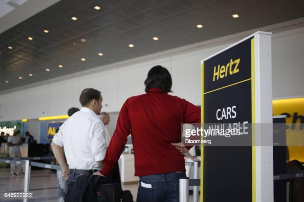 Customers wait in line at a Hertz Global Holdings Inc rental location inside Charlotte Douglas International Airport in Charlotte North Carolina US...