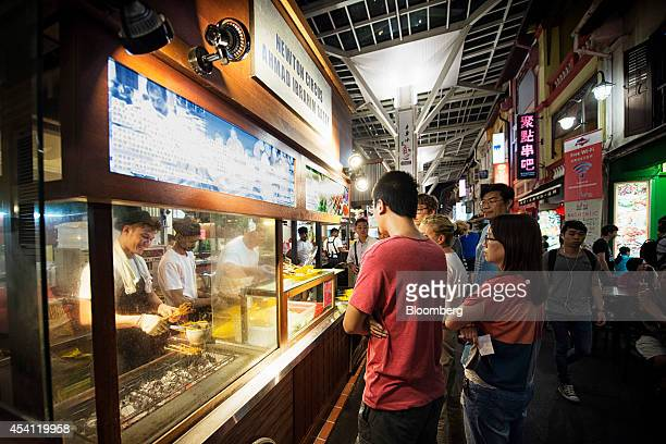 Customers wait in line at a satay stall in Chinatown Food Street in the area of Chinatown in Singapore on Saturday Aug 23 2014 Singapore is scheduled...