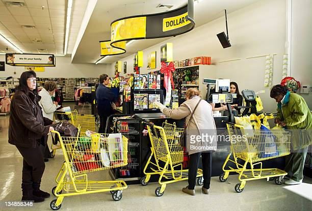 Customers wait in line at the cash resister in Dollar General Corp store in Saddle Brook New Jersey US on Saturday Dec 3 2011 Dollar General is...