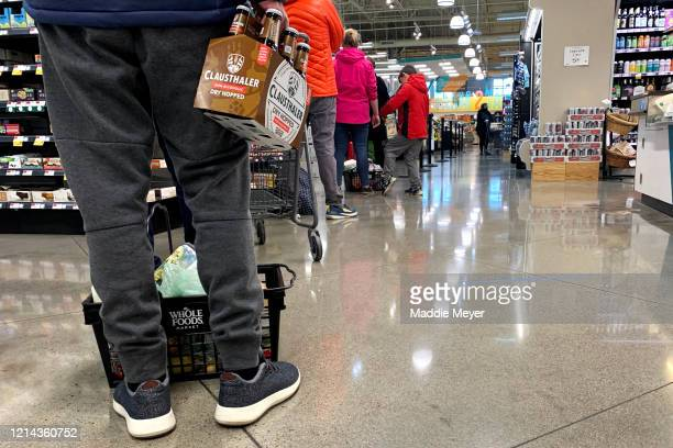 Customers wait in line at Whole Foods behind marked lines to accommodate social distancing guidelines at on March 23, 2020 in Cambridge,...