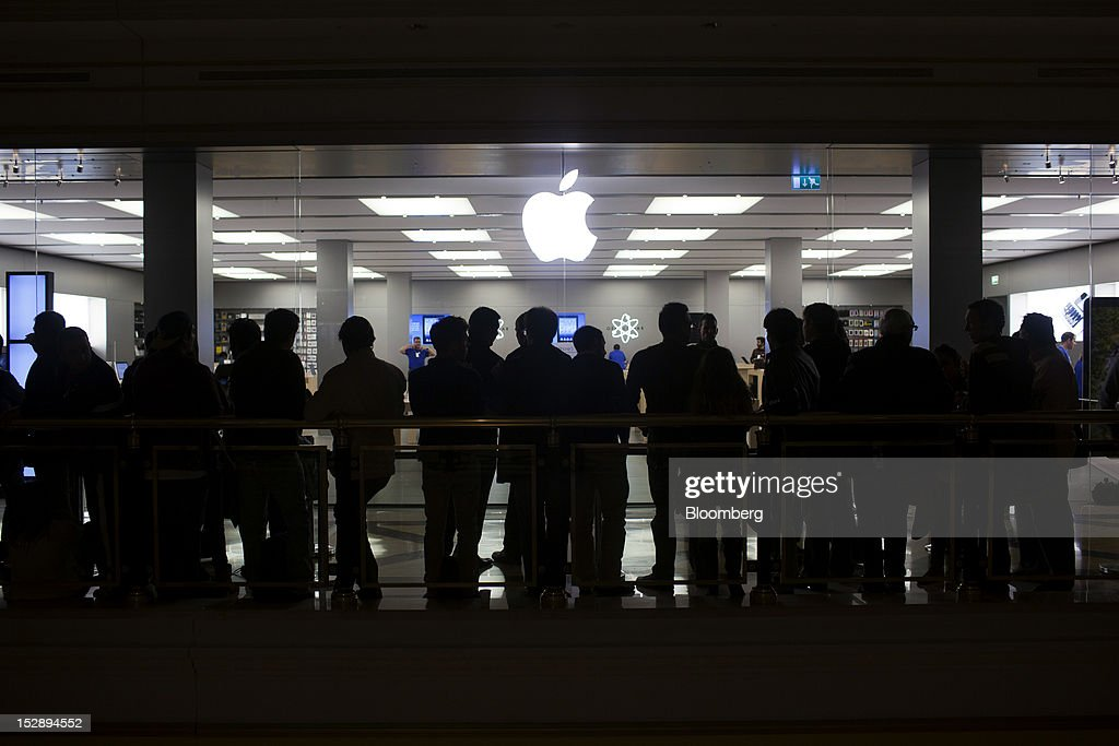 Customers wait in line for the launch of the Apple Inc. iPhone 5 outside the Apple store in the Gran Plaza 2 shopping mall in Majadahonda, near Madrid, Spain, on Friday, Sept. 28, 2012. Apple said it is working to catch up with demand, 'We are working hard to get an iPhone 5 into the hands of every customer who wants one as quickly as possible,' Apple Chief Executive Officer Tim Cook said in a statement. Photographer: Angel Navarrete/Bloomberg via Getty Images