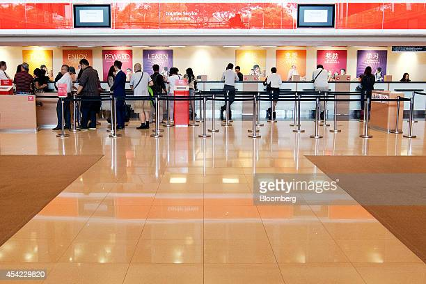 Customers wait in line inside an OverseaChinese Banking Corp bank branch at OCBC Center in Singapore on Friday Aug 22 2014 OverseaChinese Banking...