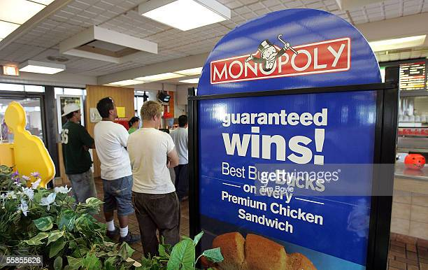 Customers wait in line near a promotional sign for the new Monopoly game in a McDonald's restaurant October 5 2005 in Niles Illinois McDonald's...