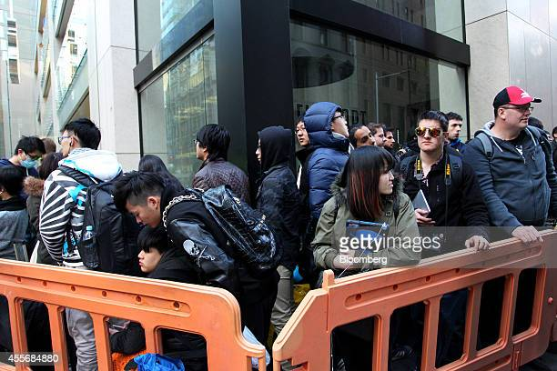 Customers wait in line outside the Apple Inc George Street store during the sales launch of the iPhone 6 and iPhone 6 Plus in Sydney Australia on...