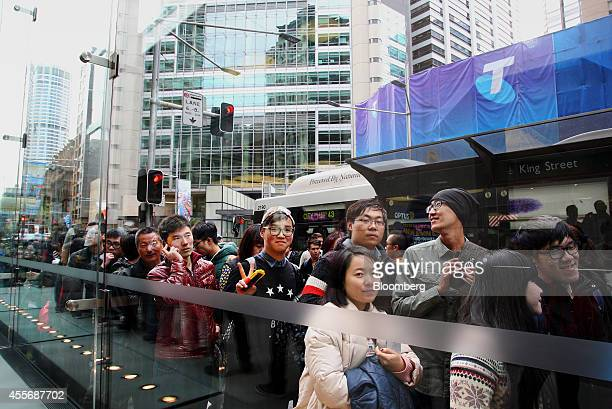 Customers wait in line outside the Apple Inc. George Street store during the sales launch of the iPhone 6 and iPhone 6 Plus in Sydney, Australia, on...