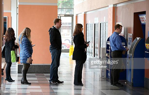 Customers wait in line to buy stamps at the United States Post Office at Rincon Center on December 17 2012 in San Francisco California Customers line...