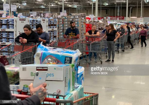 Customers wait in line to buy water and other supplies on fears that the coronavirus COVID19 will spread and force people to stay indoors at a Costco...