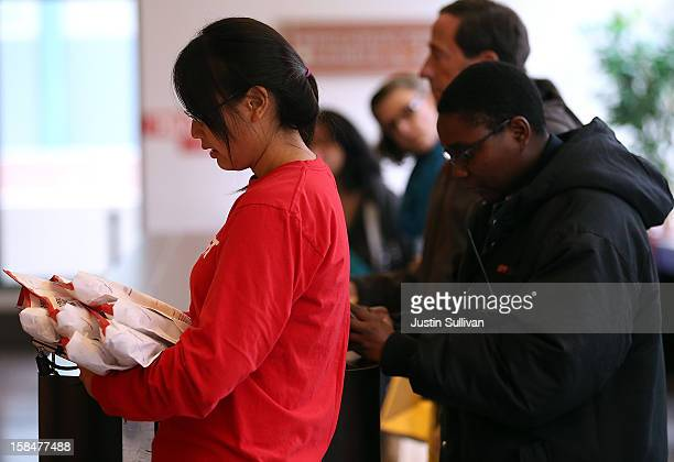Customers wait in line to deliver packages at the United States Post Office at Rincon Center on December 17 2012 in San Francisco California...