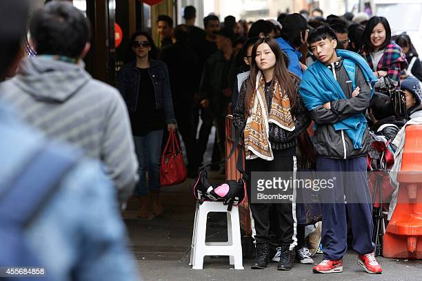 Customers wait in line to enter the Apple Inc. George Street store during the sales launch of the iPhone 6 and iPhone 6 Plus in Sydney, Australia, on...