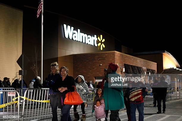 Customers wait in line to enter WalMart Thanksgiving day on November 28 2013 in Troy Michigan Black Friday shopping began early this year with most...
