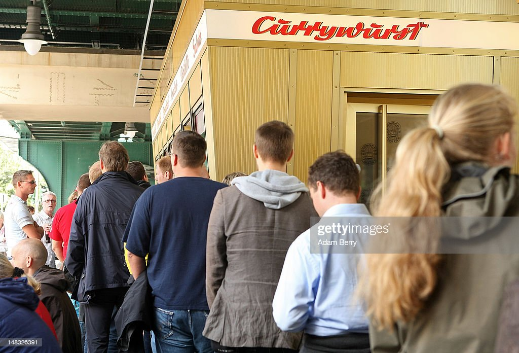 Customers wait in line to make purchases at Konnopke's currywurst stand on July 14, 2012 in Berlin, Germany. Currywurst, originally founded in post-war Berlin by Herta Heuwa, is Berlin's answer to fast food and is sold at specialized stands across the city and the rest of Germany. Currywurst is pork sausage, with or without casing, fried or deep-fried, that is typically smothered in curry powder and a ketchup-like sauce called curry sauce and served with french fries.