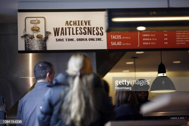 Customers wait in line to order food at a Chipotle Mexican Grill Inc restaurant in Louisville Kentucky US on Saturday Feb 2 2019 Chipotle Mexican...