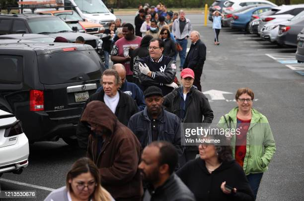 Customers wait in line to purchase bottles of hand sanitizer produced by Twin Valley Distillers March 19 2020 in Rockville Maryland The distillery is...