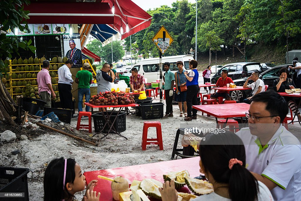 Customers wait in line to purchase durians as others sit and eat the fruit at a road side stall in Petaling Jaya, Selangor, Malaysia, on Monday, July 13, 2015. The Southeast Asian native fruit -- known for its sweet, custardy flesh and banned from Singapore's subways and hotels because of its pungent odor -- can retail for more than S$40 ($30) apiece in Singapore. Photographer: Sanjit Das/Bloomberg via Getty Images
