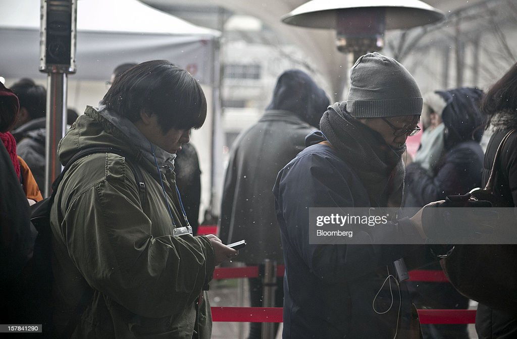 Customers wait in line to purchase the Apple Inc. iPhone 5 outside a KT Corp. Olleh brand mobile phone store in Seoul, South Korea, on Friday, Dec. 7, 2012. The iPhone 5 went on sale in South Korea today. Photographer: Jean Chung/Bloomberg via Getty Images