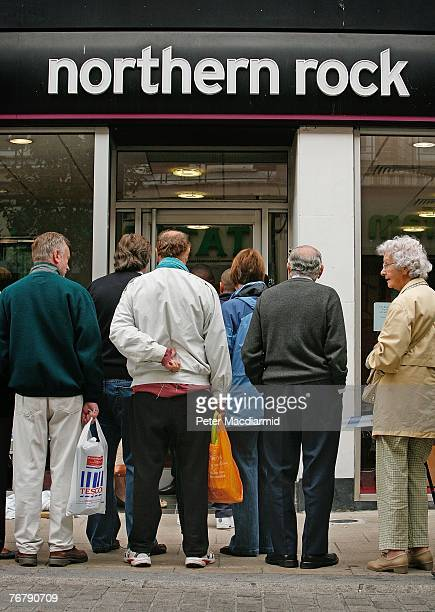 Customers wait in line to remove their savings from a branch of The Northern Rock bank on September 17 2007 in KingstonUponThames England...