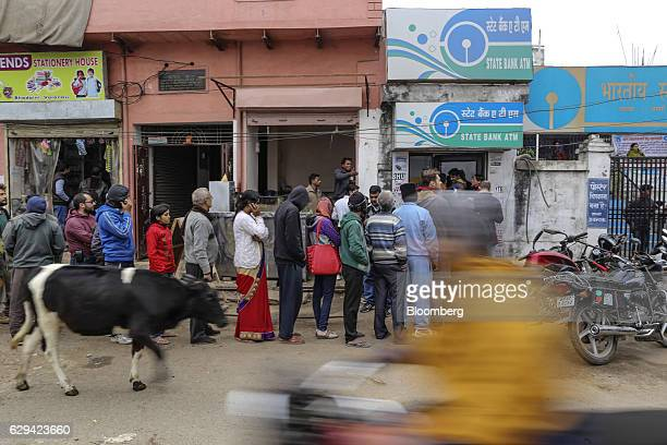 Customers wait in line to use an automated teller machine operated by the State Bank of India in Varanasi Uttar Pradesh India on Friday Dec 9 2016...
