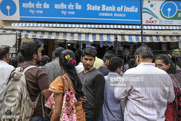 Customers wait in line to withdraw cash from a State Bank of India branch in Mumbai India on Saturday Nov 19 2016 India's top court refused to stay...
