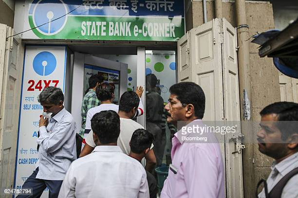 Customers wait in line to withdraw cash outside a State Bank of India branch in Zaveri Bazaar in Mumbai India on Saturday Nov 19 2016 India's top...