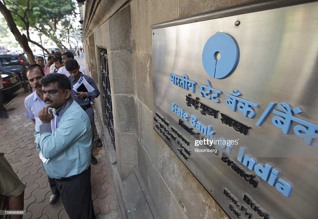 Customers wait on line for the opening of a State Bank of India bank branch in Mumbai, India, on Wednesday, Jan. 16, 2013. India's financial system has been made vulnerable by a deterioration in bank assets and a lack of capital as the economy slowed, according to the International Monetary Fund. Photographer: Kuni Takahashi/Bloomberg via Getty Images