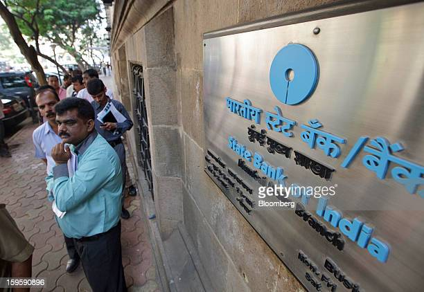 Customers wait on line for the opening of a State Bank of India bank branch in Mumbai India on Wednesday Jan 16 2013 India's financial system has...