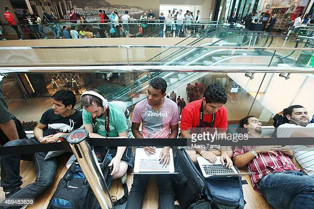 Customers wait on line to enter Brazil's first Apple retail store before it opened to the public for the first time in the Village Mall shopping...