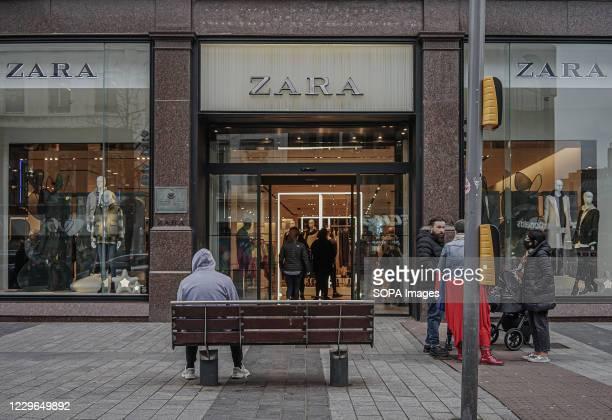 Customers wait outside a Zara store.