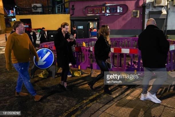 Customers wait outside the Switch bar in Newcastle as it prepares to serve customers after midnight to mark the latest lifting of lockdown measures...