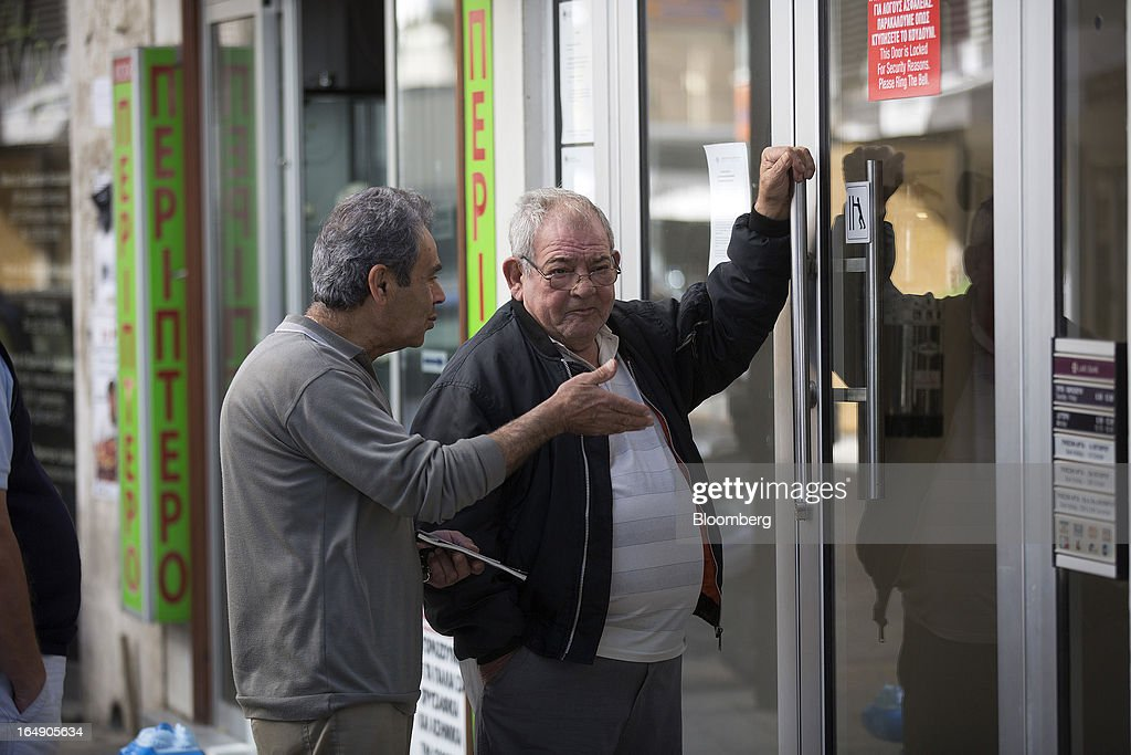 Customers wait their turn to be allowed access into a branch of a Cyprus Popular Bank Pcl, also known as Laiki Bank, in Nicosia, Cyprus, on Friday, March 29, 2013. Cypriots face a second day of bank controls over their use of the euro as officials in Europe urged the country to move quickly to lift the restrictions, the first time they have been imposed on the common currency. Photographer: Simon Dawson/Bloomberg via Getty Images